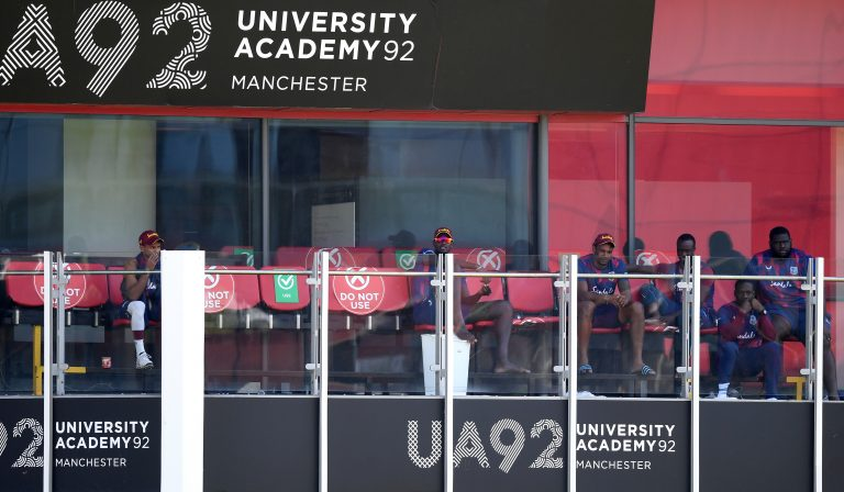 West Indies players look on from the dressing room balcony at Old Trafford
