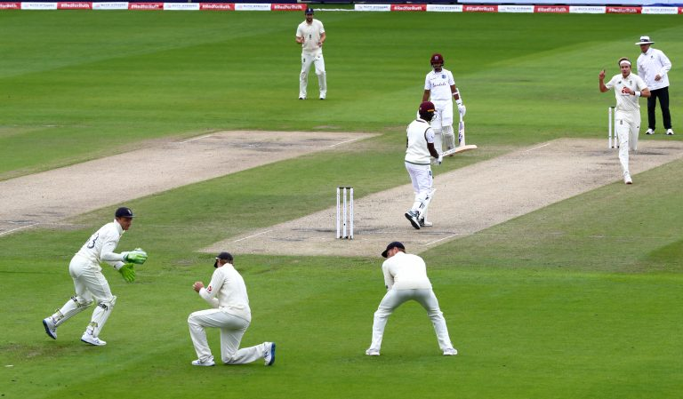 Kemar Roach is caught at slip by Joe Root, second left