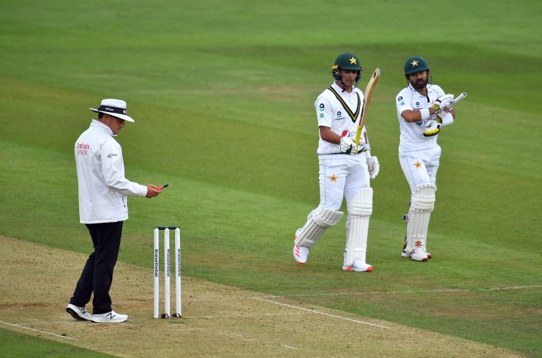 Pakistan's Mohammad Rizwan and Naseem Shah leave the pitch for bad light as the umpire takes a light reading