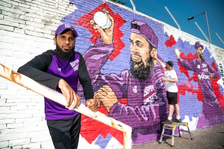Rashid is the subject of a new mural by artist Adam Duffield (background). (Simon Dewhurst).